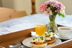 Eggs Benedict on breakfast tray on bed Royalty Free Stock Photos