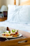Eggs Benedict on breakfast tray on bed Stock Photography