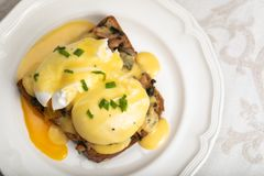 Eggs Benedict for brunch. Close up of poacheg eggs with bacon, shpinach and hollandaise sause royalty free stock images