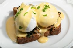 Eggs Benedict for brunch. Close up of poacheg eggs with bacon, shpinach and hollandaise sause royalty free stock photos