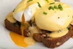 Eggs Benedict for brunch. Close up of poacheg eggs with bacon, shpinach and hollandaise sause stock photography
