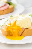 Eggs benedict. Close up on white plate, serving table Stock Images