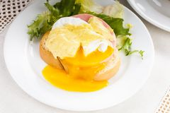 Eggs benedict. Close up on white plate, serving table Royalty Free Stock Photo
