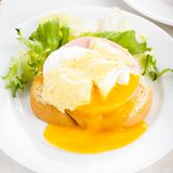 Eggs benedict. Close up on white plate, serving table Royalty Free Stock Photos