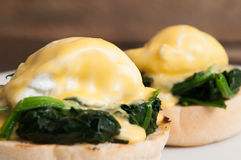 Eggs benedict or eggs florentine on a white plate in the cafe Stock Image