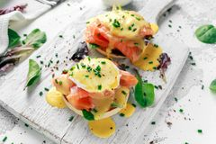 Eggs Benedict on english muffin with smoked salmon, lettuce salad mix and hollandaise sauce on white board Royalty Free Stock Photos