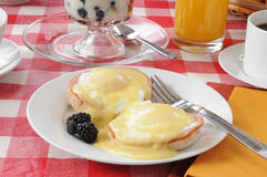 Eggs benedict with fruit cocktail Stock Photos