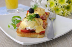 Eggs Benedict with ham and tomato on toast with cheese Stock Photography