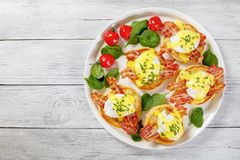 Eggs Benedict on a platter. Eggs Benedict - toasted English muffins, fried crispy bacon, poached eggs and classic buttery hollandaise sauce sprinkled with finely Stock Photo