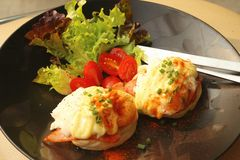 Eggs Benedict ,vegetable ,eggs on a black plate. Royalty Free Stock Images