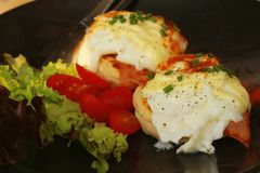 Eggs Benedict ,vegetable ,eggs on a black plate. Stock Photography