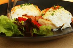 Eggs Benedict ,vegetable ,eggs on a black plate. Royalty Free Stock Image