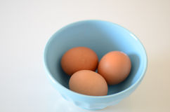Eggs. On blue bowl over white background Stock Photo