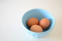 Eggs. On blue bowl over white background Stock Images