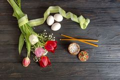 Eggs, a bouquet of tulips, incense and church candles. The easter composition. Eggs, a bouquet of tulips, incense and church candles on wooden table close-up Stock Image