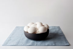 Eggs in a bowl on blue napkin from side Stock Photography
