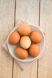 Eggs in a bowl. Brown green eggs on a handmade plate on wood stock photo
