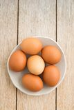Eggs in a bowl. Brown green eggs on a handmade plate on wood royalty free stock photos
