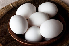 Eggs in a bowl on cutting board closeup from above Stock Photos