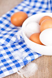 Eggs in a bowl, towel and feather Royalty Free Stock Photos