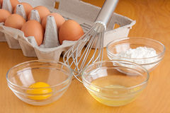 Eggs, Bowls and a Whisk. Separated cracked eggs in glass bowls, flour in a glass bowl, a silver whisk, and carton of eggs all on a cutting board royalty free stock images