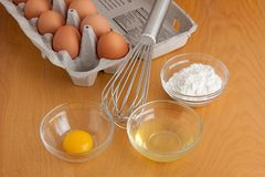 Eggs, Bowls and a Whisk. Separated cracked eggs in glass bowls, flour in a glass bowl, a silver whisk, and carton of eggs all on a cutting board stock image