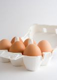 Eggs in a box. Six eggs in an open box, over a white background royalty free stock image