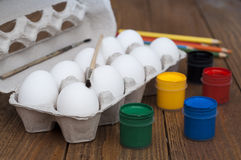 Eggs in the box. Paints, brushes and pencils. Eggs in the package. Paints, brushes and pencils. Happy Easter Royalty Free Stock Photos