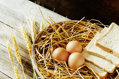 Eggs and bread in the basket. With still life Stock Photos