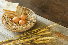 Eggs and breads in the basket. With wooden background Stock Images