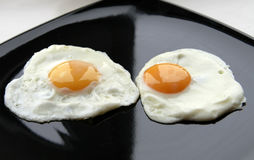Eggs breakfast. Two fried eggs on the black plate Stock Photo