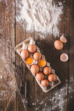 Eggs and broken eggs in the package on a wooden background. Were scattered flour on a wooden table. Stock Photography