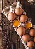 Eggs and broken eggs and quail eggs in the package on a wooden background. Rustic Style. Eggs. Easter photo concept. Royalty Free Stock Image
