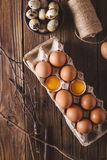 Eggs and broken eggs and quail eggs in the package on a wooden background. Rustic Style. Eggs.  Easter photo concept. Stock Photos