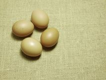 Eggs on brown Hessian sackcloth woven texture background royalty free stock image