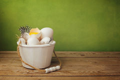 Eggs in bucket on wooden table over green background Royalty Free Stock Photography