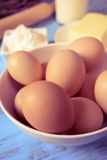 Eggs, butter, flour and milk on a blue wooden table Stock Photos