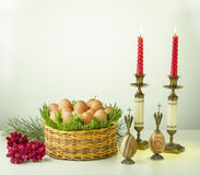 Eggs, candlesticks, angels, candles, basket, grass, stone. Festive greeting card on white background with eggs, candlesticks, angels, candles, basket, grass Stock Image