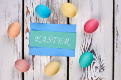 Eggs and card on wood. Simple Easter greeting card Stock Image