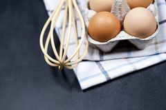 Eggs in cardboard box, towel and whisker closeup on backboard background. Eggs, whisker, towel and other cooking baking ingredients for cake, pastry or cookies royalty free stock image