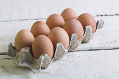Eggs in a cardboard tray on a white boards. Royalty Free Stock Images