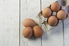 Eggs in a cardboard tray on a white boards. Stock Photos