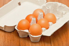 Eggs in the cardboard on the wooden background Royalty Free Stock Image