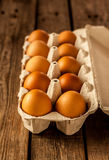 Eggs in a carton box on vintage rustic wood. Natural gold eggs in a carton box on an old vintage planked wood table. Easter - rural or rustic kitchen still life Stock Photos