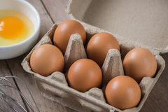 Eggs in carton box and yolk in bowl Stock Photography