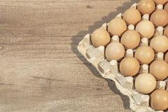 Eggs in carton package on a wooden table ready for baking. Close Royalty Free Stock Photography