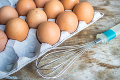 Eggs in carton and Whisk. Eggs in the carton will be safe because the egg carton is a carton designed for carrying and transporting whole eggs Stock Image