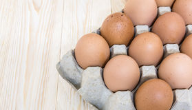 Eggs. In carton on wooden background Royalty Free Stock Images