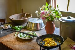 Eggs in a Cast Iron Skillet - Kitchen Table. Scrambled Eggs in a cast iron skillet on a kitchen table with herbs, eggs, a wooden bowl, pot, and a flower vase stock photo