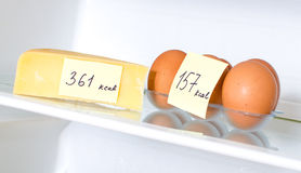 Eggs and cheese. With marked calories on fridge shelf Royalty Free Stock Image
